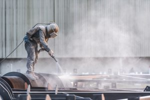 Worker doing concrete sandblasting