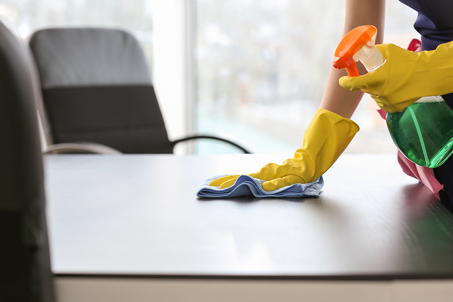 professional office cleaner in Sydney wiping an office table